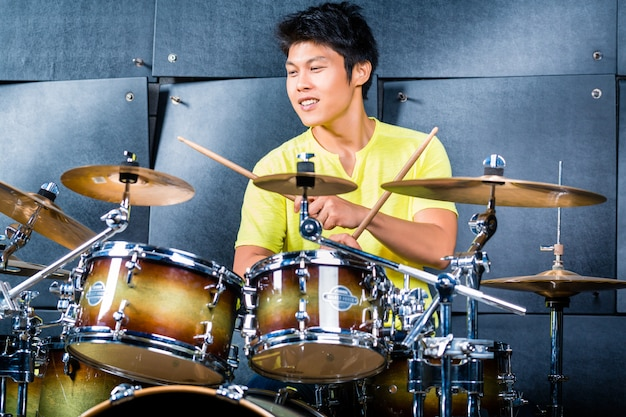 Musicien asiatique batteur en studio d'enregistrement Photo Premium