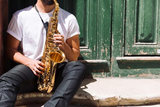 Musicien jouant du saxo dans la rue Photo gratuit