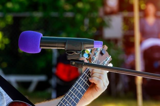 Un Musicien Jouant De La Guitare Acoustique Derrière Un Microphone à Condensateur Lors De L'enregistrement Photo Premium