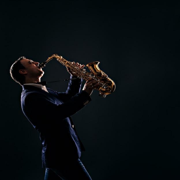Musicien joue du jazz au saxophone. sombre Photo Premium