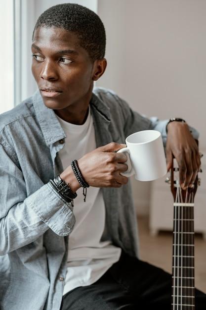 Musicien Masculin Avec Guitare Et Tasse Photo gratuit