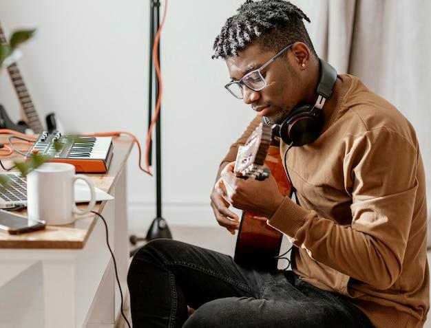 Musicien Masculin Sérieux à La Maison à Jouer De La Guitare Et Mélanger Avec Un Ordinateur Portable Photo gratuit