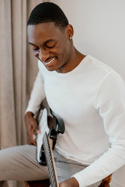 Musicien Masculin Smiley Avec Guitare Photo gratuit