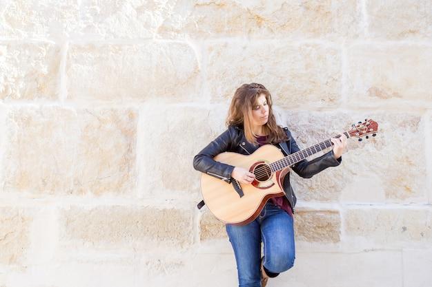 Musicienne De Rue Songeuse Jouant De La Guitare Photo gratuit