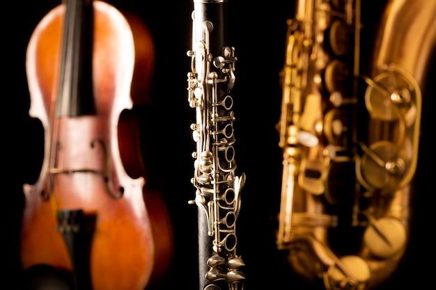 Musique saxophone ténor saxophone violon et clarinette en noir Photo Premium