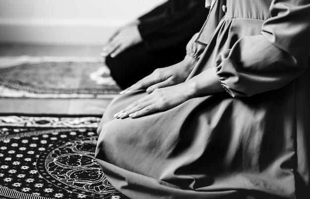 Musulman priant dans la posture de tashahhud Photo gratuit