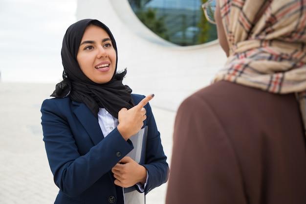 Une musulmane excitée consulte un collègue consultant à l'extérieur Photo gratuit