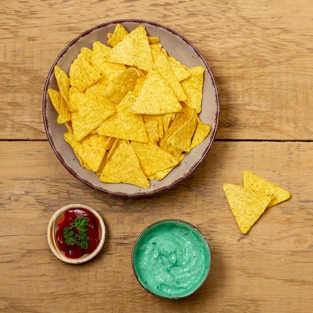 Nachos sur assiette et diverses sauces sur table en bois Photo gratuit