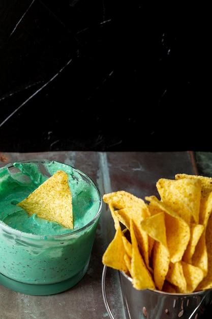 Nachos dans un seau et sauce verte dans un bol sur la table Photo gratuit