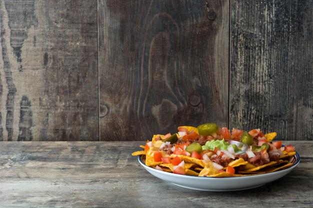 Nachos Mexicains Au Boeuf, Guacamole, Sauce Au Fromage, Poivrons, Tomates Et Oignons En Plaque Sur Fond De Bois Photo Premium