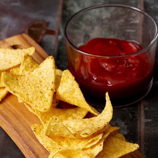 Nachos Sur Une Planche En Bois Et Sauce Tomate Dans Un Bol Photo gratuit