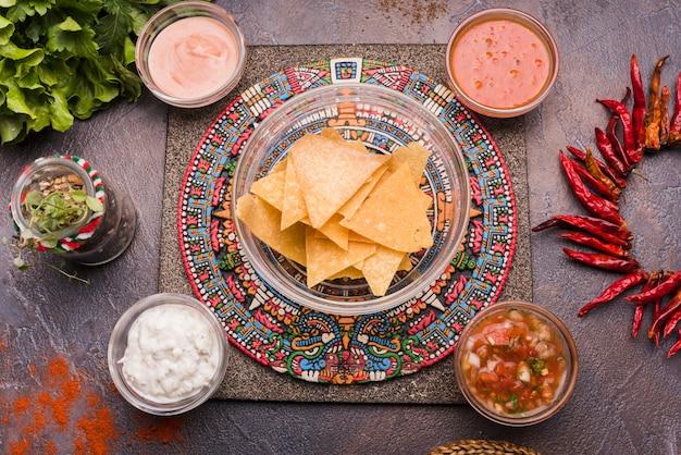 Nachos près du poivre et sauce dans des bols placés sur un plateau créatif Photo gratuit