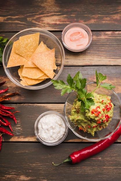 Nachos près de guacamole et sauce dans des bols de piment Photo gratuit
