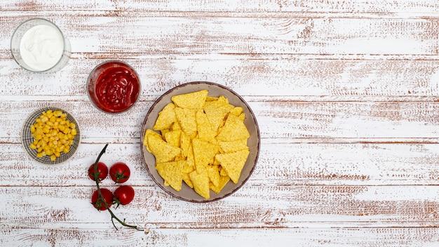 Nachos traditionnels croustillants avec trempettes et maïs Photo gratuit