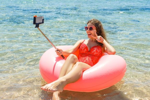 Nage fou avec beignet gonflable fait selfie sur la plage en été ensoleillé Photo Premium