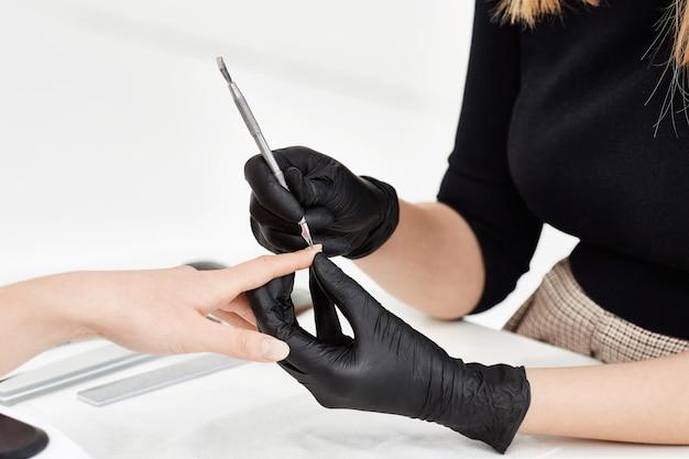 Nail Artiste Faisant Manucure Au Salon. Utilisation D'outils De Manucure. Photo gratuit