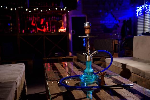 Narguilé sur le fond d'un bar, lumière, fumée, smog Photo Premium