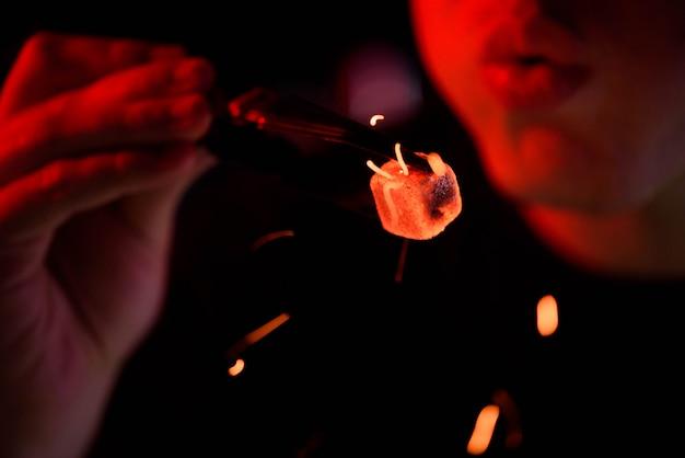 Narguilé shisha, charbons ardents rouges. l'homme souffle des braises pour voler des étincelles. Photo Premium