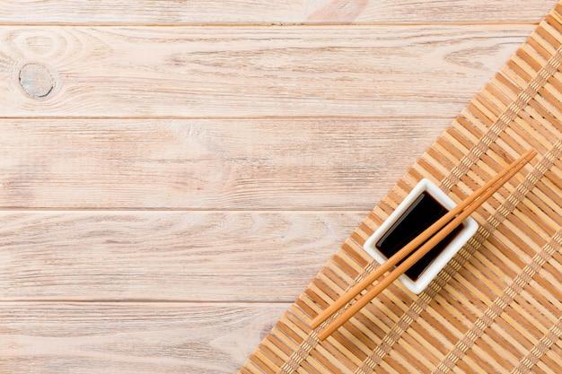 Natte De Bambou Et Sauce Soja Avec Des Baguettes De Sushi Sur Table En Bois. Vue De Dessus Avec Fond D'espace Copie Pour Les Sushis. Mise à Plat Photo Premium