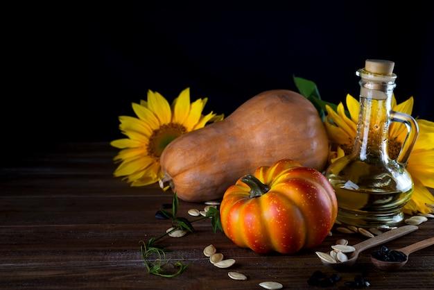 Nature morte d'automne avec citrouilles, huile et tournesol Photo Premium