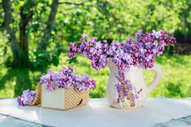 Nature morte avec une boîte lilas sur une serviette de table dans un écrin de verdure Photo Premium