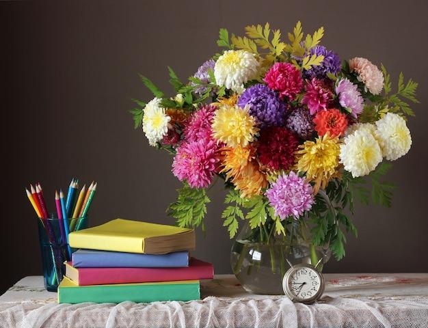 Nature morte avec bouquet d'automne et des livres. Photo Premium