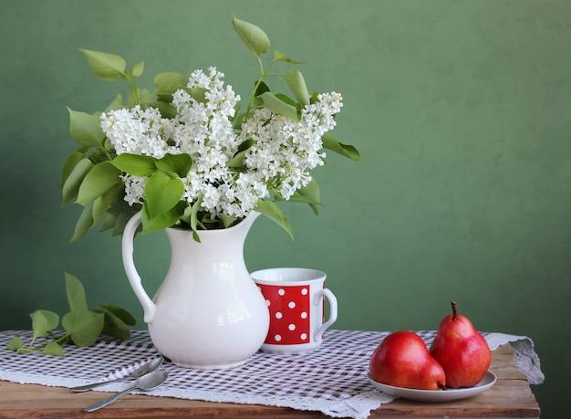 Nature morte avec un bouquet et des fruits dans un style rustique. lilas blanc et poires rouges. fleurs dans un vase. Photo Premium