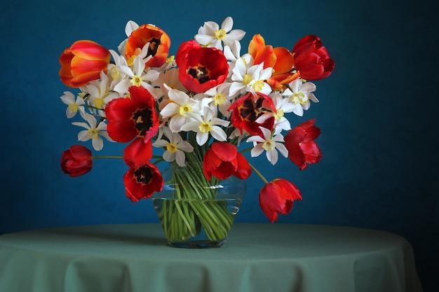 Nature morte avec un bouquet de jonquilles et de tulipes sur fond bleu. Photo Premium
