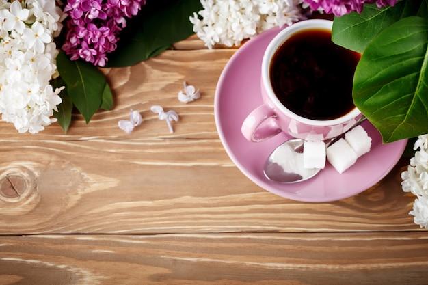 Nature Morte Avec Des Branches De Lilas Et Une Tasse De Café Sur Une Table En Bois. Photo Premium