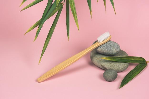 Nature Morte Avec Des Brosses à Dents En Bambou, Des Pierres Et Des Feuilles De Bambou Sur Fond Rose Photo Premium