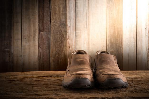 Nature morte avec des chaussures pour hommes sur une table en bois contre le mur de grunge Photo Premium
