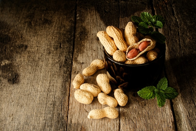 Nature morte coquille ouverte d'arachide pour montrer la graine dans le côté sur le bois Photo Premium