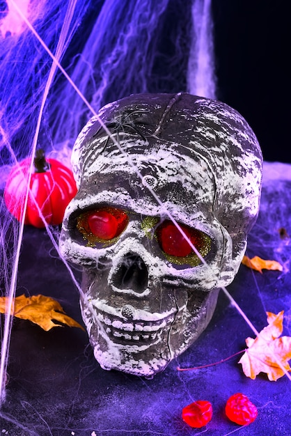Nature morte avec crâne humain et feuilles d'automne, araignée sur halogène violet noir Photo Premium