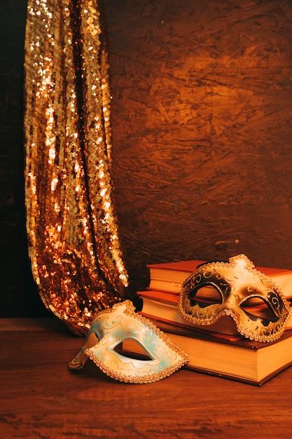 Nature morte de deux masque de carnaval vénitien avec des livres sur fond texturé sombre Photo gratuit