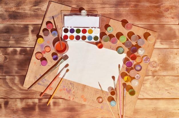 Nature morte avec du papier vierge, des pinceaux et des pots d'aquarelle et de gouache Photo Premium