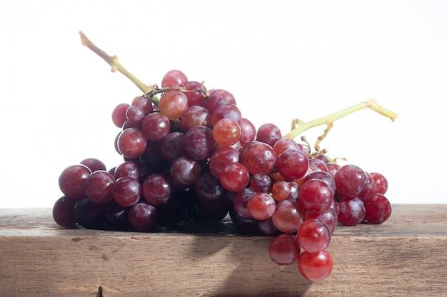 Nature morte de fruits de raisin mis sur vieux bois, fond blanc Photo Premium