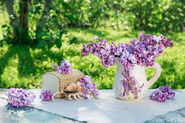 Nature morte avec lilas, cercueil, coquille posée sur une serviette de table sur fond de verdure Photo Premium