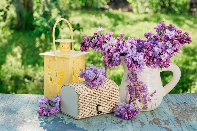 Nature morte avec un lilas dans un pichet, un cercueil, une lampe de poche sur une table en bois sur un fond de verdure Photo Premium