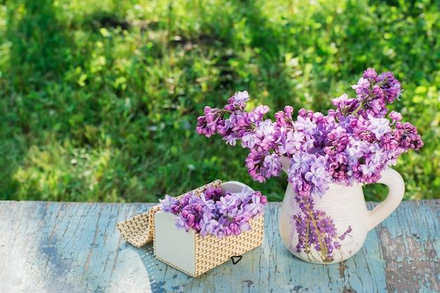 Nature morte avec un lilas dans un pichet, un cercueil sur une table en bois sur un fond de verdure Photo Premium