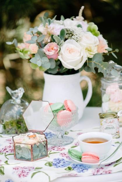 Nature morte mariées matin, plat avec une tasse de thé, verre à champagne, alliances et bouquet de fleurs Photo Premium