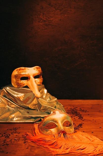 Nature morte de masque de carnaval vénitien avec des plumes sur fond texturé noir Photo gratuit
