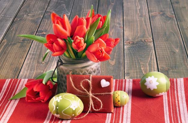 Nature morte de pâques avec tulipes rouges, cadeau emballé et oeufs de pâques sur bois Photo Premium