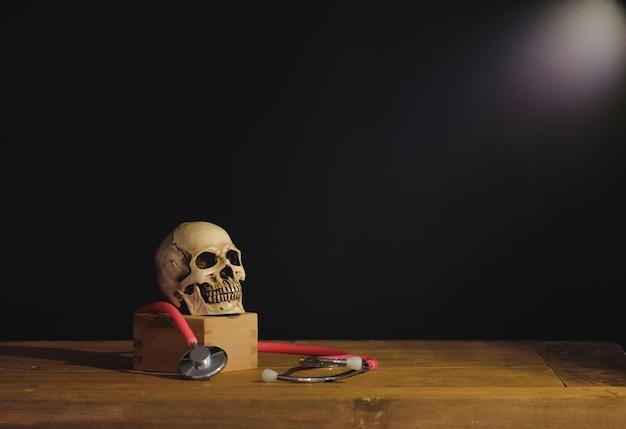 Nature morte peinture photographie avec crâne humain sur le livre de texte. Photo Premium