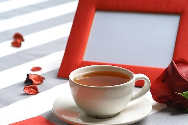 Nature morte romantique avec une tasse de thé et des attributs de vacances rouge vif. Photo Premium