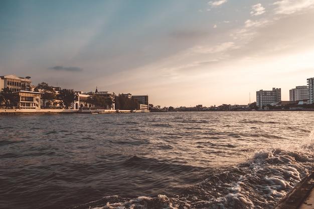 Navigation de plaisance sur la rivière chao phraya dans la soirée et observation de la colonisation locale le long de la rivière. Photo Premium