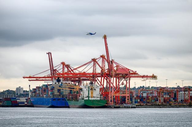 Navire cargo international avec conteneurs, grues et hélicoptère volant Photo Premium