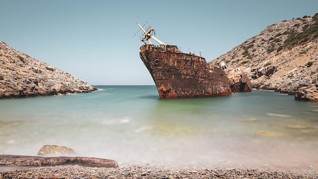 Navire Rouillé Abandonné Dans La Mer Près D'énormes Formations Rocheuses Sous Le Ciel Clair Photo gratuit