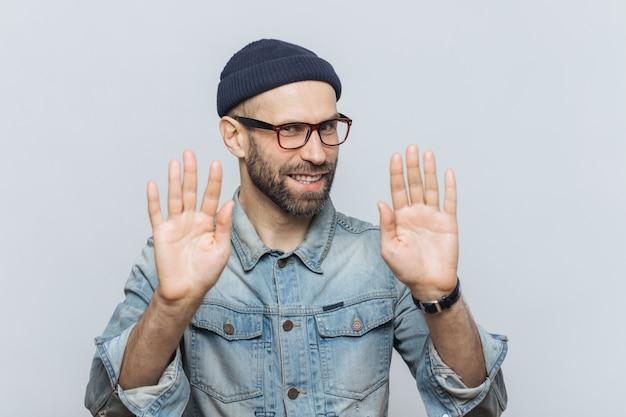 Ne me dérange pas! enthousiaste mâle d'apparence agréable montre un panneau d'arrêt, demande de ne pas lui parler Photo Premium