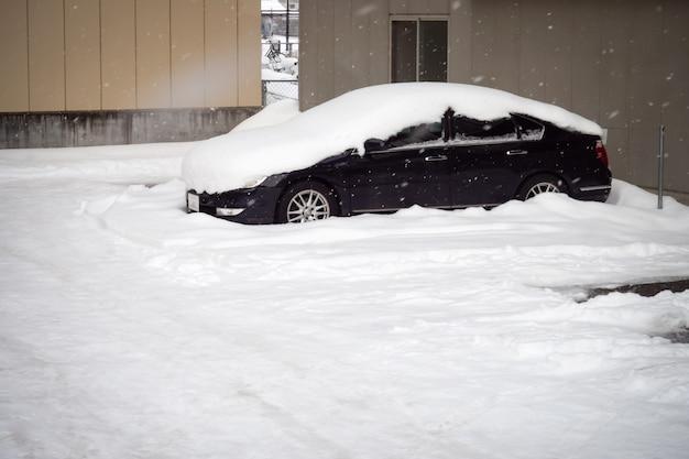 Neige couvrir le toit de la voiture dans le parking. l'hiver. Photo Premium