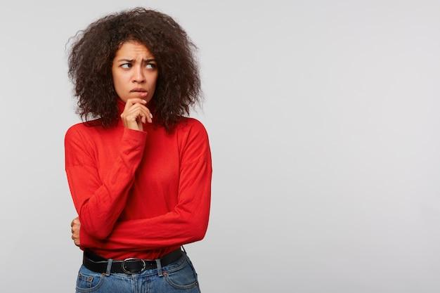 Nerveuse Jeune Femme Inquiète Avec Une Coiffure Afro, Regarde De Côté à L'espace Copie Vierge Avec Une Expression Réfléchie, Garde Le Poing Près Du Menton Photo gratuit